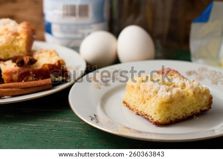 Horizontal photo of One slice of apple pie in kitchen with ingredients, other portions, eggs and flour placed on green worn table - stock photo