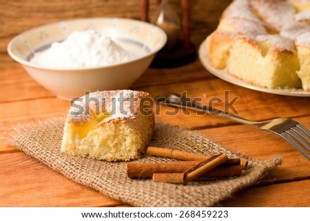 Horizontal photo of Portion of curd cake together with cinnamon on jute cloth, fork and bowl with powder sugar plus other portions in background - stock photo