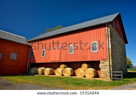 Horizontal photo of red barn with stone wall and bales of hay - stock photo