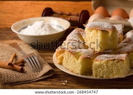 Horizontal photo of Several portions of curd cake on a plate, fork and cinnamon on jute cloth on left. Eggs in box plus bowl with powder sugar in background - stock photo