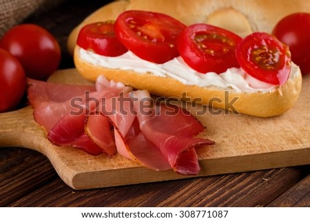 Horizontal photo of Slice of prosciutto ham on chopping board with fresh baguette. Cream cottage cheese is on baguette with few slices of tomato. - stock photo