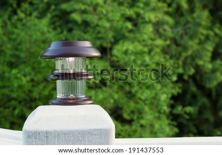 Horizontal photo of solar lamp, light just turning on, on patio post with green trees in background  - stock photo