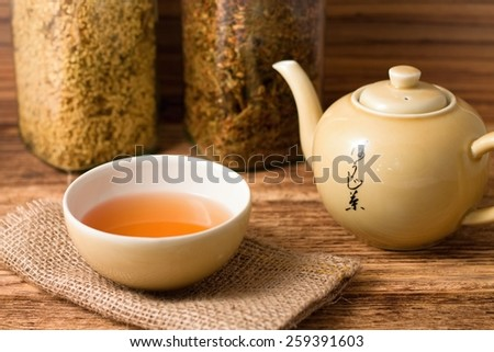 Horizontal photo of tea in oriental bowl placed on jute cloth near a tea pot with chinese signs and with two jars full of dry herbs - stock photo