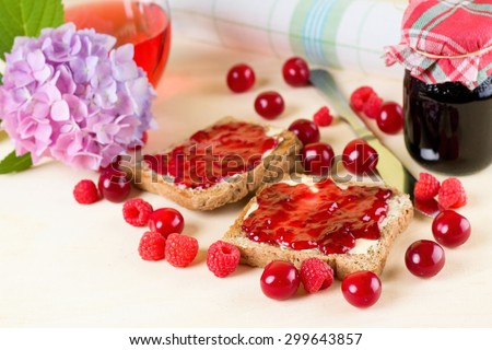 Horizontal photo of two toasts with butter and homemade marmalade among cherries and raspberries. Hydrangea, jar with jam, knife and towel are around on wooden board. - stock photo