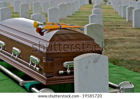 Horizontal photo of yellow and red rose on casket at Arlington National Cemetery with gravestones in background - stock photo