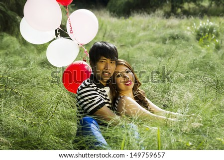 Horizontal photo of young adult couple, looking forward, sitting in the middle of a green tall grass field with several red and white balloons behind them  - stock photo