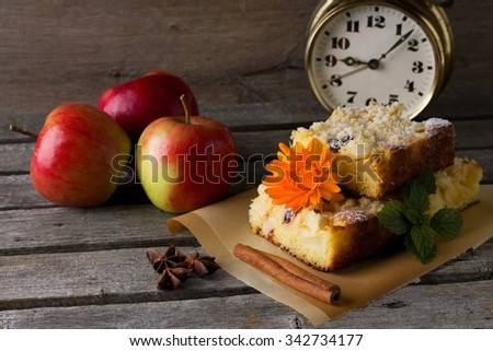 Horizontal photo with few slices of apple cake with raisins, marigold bloom and melissa on brown paper with spices. Alarm clock is in background on wooden board.  - stock photo