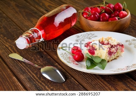 Horizontal photo with white plate with two cherries, herb leaves and portion of fruit cake. Fruit fresh lemonade, spoon and bowl full of cherries are in back. It is on wooden table. - stock photo