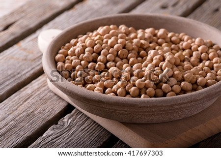 Horizontal photo. Yellow dry chickpeas. Chickpeas in clay bowl. Earthen plate with legumes. Bowl on chopping board. Bowl on old wooden board. Old worn wooden board with grey color. - stock photo