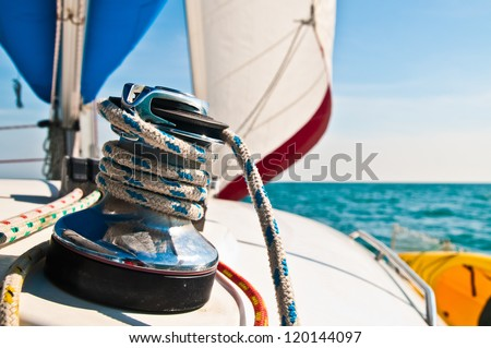 Horizontal photograph of a blue and white line wrapped around a large metal cleat with white and red sail set in background. - stock photo