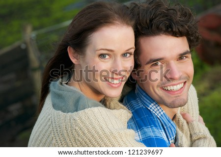 Horizontal portrait of a young, happy, smiling couple outdoor. Caucasian boyfriend and laughing girlfriend are enjoying the outdoors. - stock photo