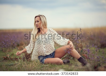 Horizontal portrait of one caucasian woman with long blond hair dressed in white shirt and jeans shorts and high shoes sitting on the grass on green field in autumn - stock photo