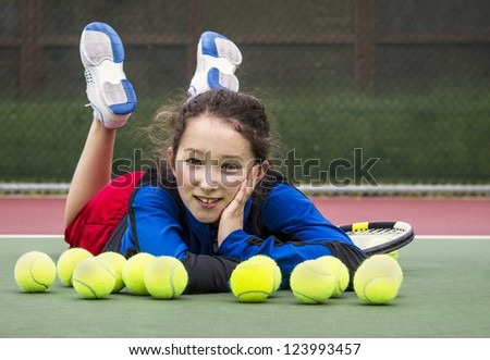 Horizontal portrait of smiling teenage girl tennis player laying on the outdoor court behind a row of tennis balls with head resting in her hand and feet in air - stock photo