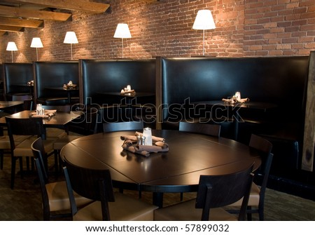Horizontal restaurant interior with round tables, booths, and lamps - stock photo