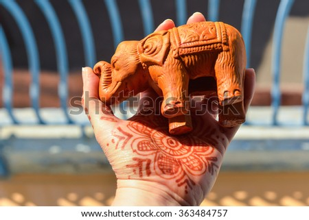 """Horizontal, selective focus shot of a white hand with henna design, holding a ceramic elephant. This was shot on a balcony in Jodhpur, India, the """"Blue City"""". - stock photo"""