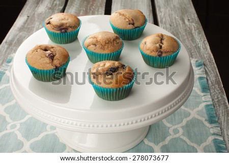 Horizontal shot of a white cake stand with fresh homemade blueberry whole wheat muffins - stock photo