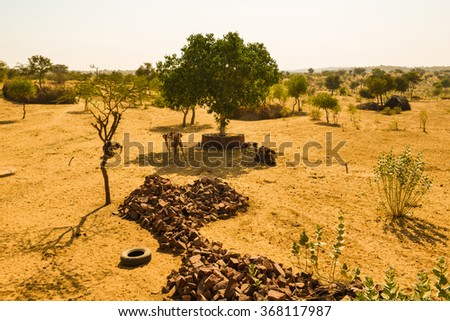 Horizontal shot of three camels with their riding saddles on. They are resting in the shade after a ride through the desert. This was shot in the Thar Desert in India.  - stock photo