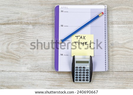 Horizontal top view of an office wooden desktop with small calendar, calculator and sharpen blue pencil with reminder of doing Tax Returns.  - stock photo