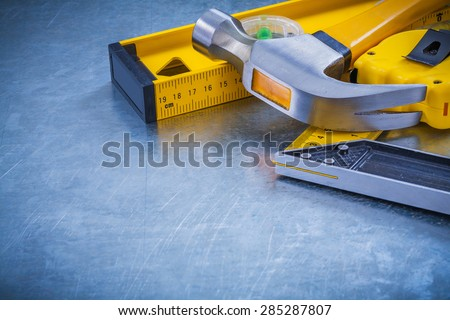 Horizontal version of claw hammer tape measure construction level square ruler on metallic background maintenance concept. - stock photo