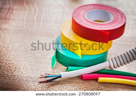 horizontal view electric cable in corrugated pipe rolls of isulating tape heat shrinkable tubes on wooden board  - stock photo