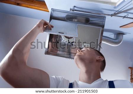 Horizontal view of a handyman fixing kitchen wall hood - stock photo