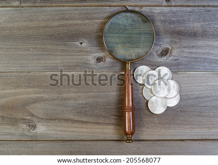 Horizontal view of an antique round shaped magnifying glass and a pile of old silver dollar coins on rustic wood  - stock photo