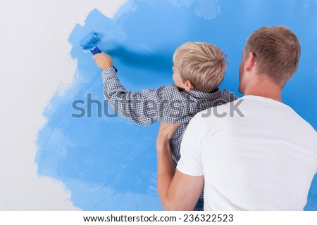 Horizontal view of boy painting wall in dad's arms - stock photo