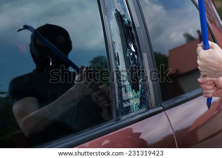 Horizontal view of car robber with crowbar - stock photo