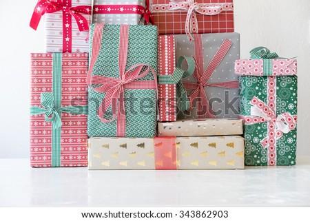 Horizontal view of christmas presents on white table. - stock photo