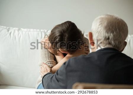 Horizontal view of grandpa comforting his crying granddaughter - stock photo