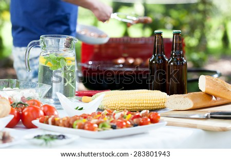 Horizontal view of host grilling tasty sausages - stock photo
