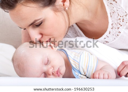 Horizontal view of mother kissing her baby - stock photo