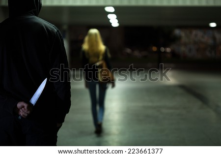Horizontal view of murderer following the victim - stock photo