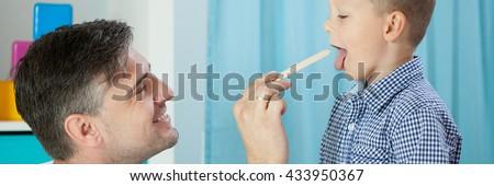 Horizontal view of pediatrician examining boy's throat - stock photo