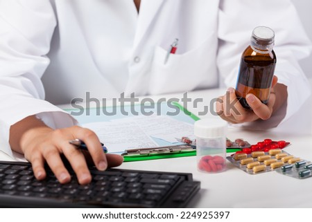 Horizontal view of pharmacist's hands selling syrup - stock photo