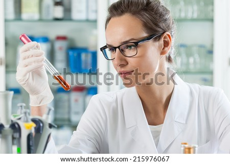 Horizontal view of scientist analyzing chemical liquid - stock photo