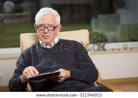Horizontal view of senior psychotherapist holding clipboard - stock photo