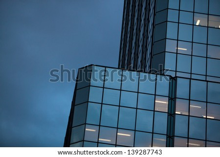 Horizontal view of sky and mirrored building at dusk. Fluorescent office light fixtures can be seen in some windows. - stock photo