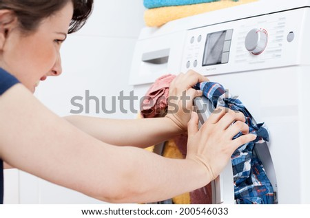 Horizontal view of young housekeeper learning to launder - stock photo