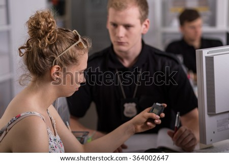 Horizontal view of young woman holding breathalyzer - stock photo