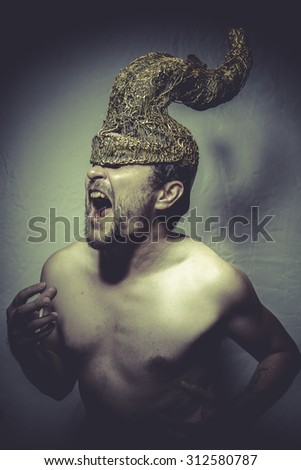 Horned, naked man with helmet warrior trumpets, and pain nightmare - stock photo