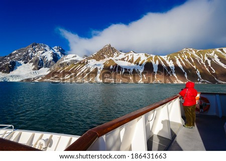 HORNSUND, SVALBARD,NORWAY - JULY 26, 2010:  Photographer on the National Geographic Explorer cruise ship in the Arctic. - stock photo