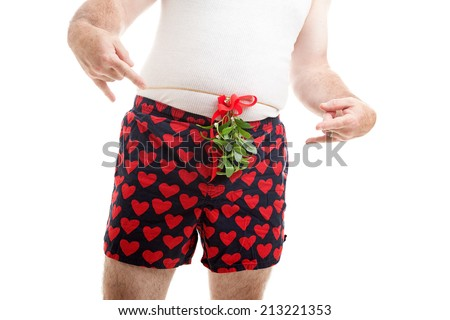 Horny guy wearing his underwear, with Christmas mistletoe tied over his boxer shorts.  White background. - stock photo