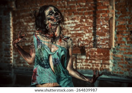 Horrible bloody zombie girl standing outdoor by the brick wall. Halloween.  - stock photo