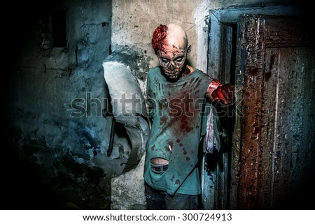 Horrible scary zombie man on the ruins of an old house. Horror. Halloween.  - stock photo