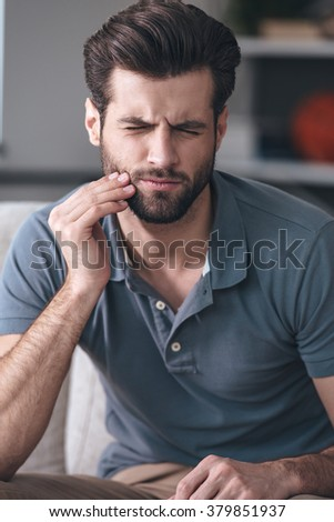 Horrible toothache. Frustrated young man touching his cheek and keeping eyes closed while sitting on the couch at home - stock photo