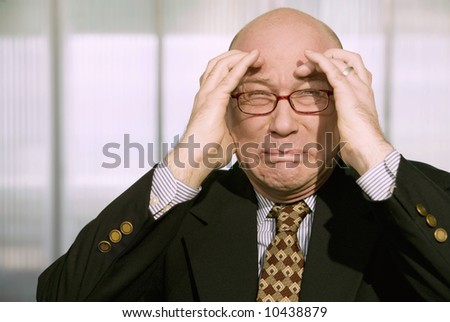 Horrified businessman with a hands to his forehead - stock photo