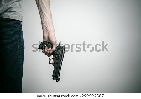 Horror and firearms topic: crazed killer with a gun on a gray background in the studio - stock photo