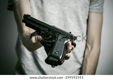 Horror and firearms topic: the killer with a gun on a gray background in the studio - stock photo