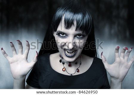Horror and halloween concept. Fashion portrait of female vampire at the night. Gothic style woman - stock photo